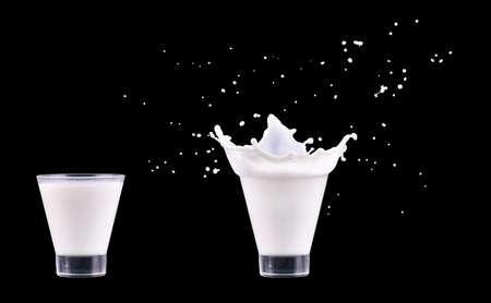 White fresh milk splash in glass on black background Stok Fotoğraf