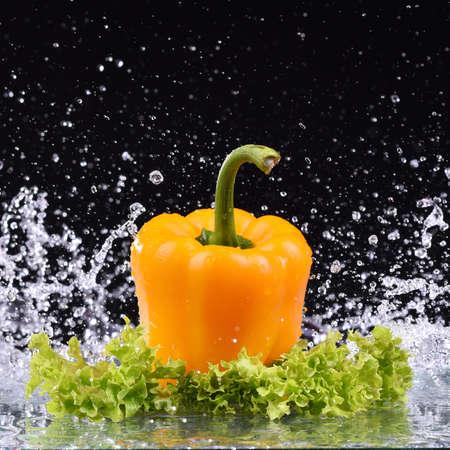 Macro yellow pepper and salad with water drop splash