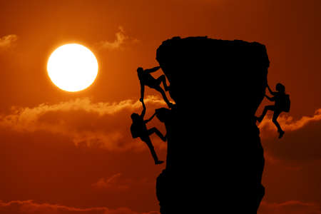 The joint work teamwork of two men travelers help each other on top of a mountain climbing team, a beautiful sunset landscape Stok Fotoğraf