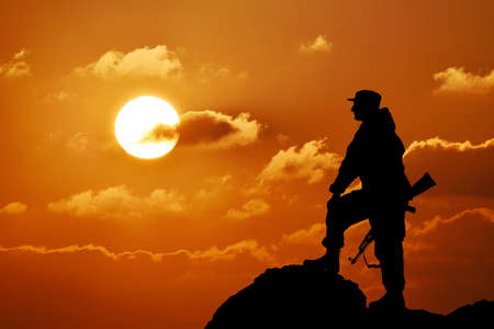 Silhouette of military soldier or officer with weapons at sunset, shot, holding gun, colorful sky, mountain in background