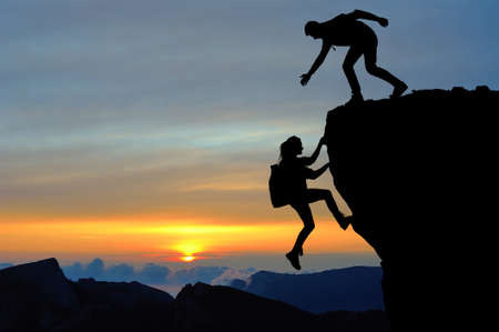 The joint work teamwork of two people man and girl travelers help each other on top of a mountain climbing team, a beautiful sunset landscape. Stok Fotoğraf