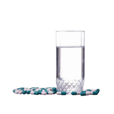 Glass with water and pills isolated on white