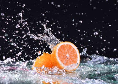 Macro water splash on orange. Water drops with juicy orange
