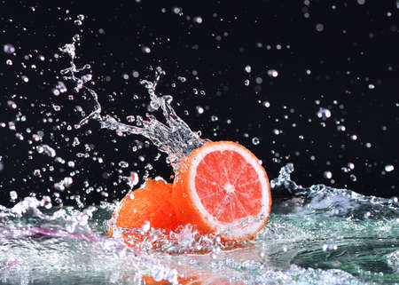 Macro water splash on grapefruit. Water drops with juicy grapefruit