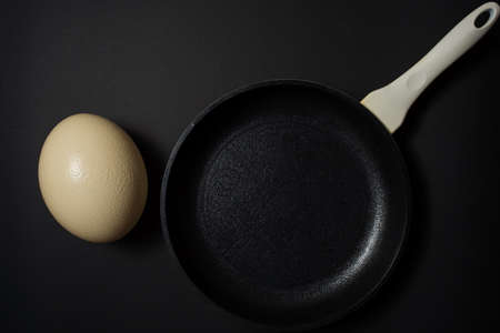 Ostrich egg on pan at black background Stok Fotoğraf