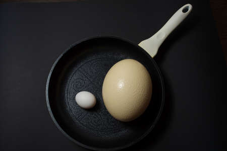 Ostrich and chicken egg on pan at black background