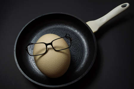 Ostrich egg with glasses on pan at black background