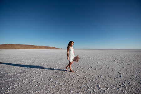 Beautiful woman with flowers walking in white dress at the salt lake
