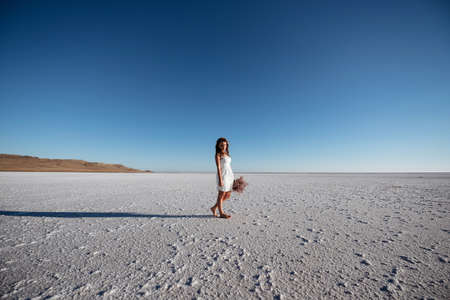 Girl in white dress with flowers in salt lake at sunset Stok Fotoğraf