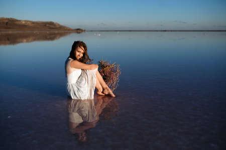 Girl in white dress sitting in salt lake with flowers at sunset. look like bride