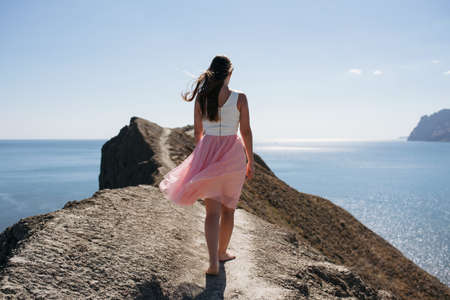 Girl in pink skirt walking at cape near sea in sunny weather