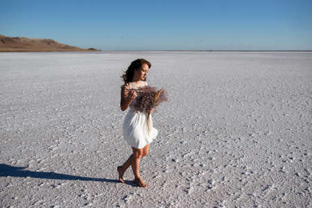 Girl in white dress at the salt lake walking with flowers. look like bride at sunset