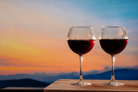 Glasses of red wine against sunset, red wine on the sky background with clouds