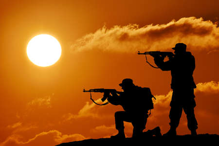 Silhouette of team soldier or officer with weapons at sunset Reklamní fotografie