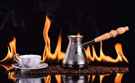 Fired cup of coffee with coffee beans and turk on dark background Standard-Bild