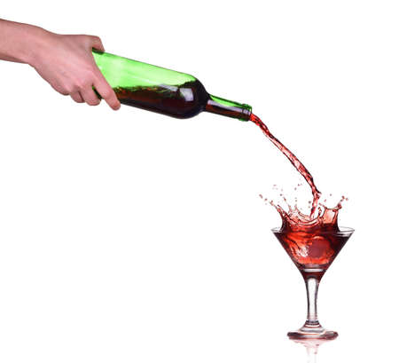 Red wine splash in the glass, pouring from a bottle Standard-Bild