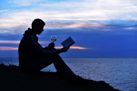Man reading book with wine on sunset Standard-Bild