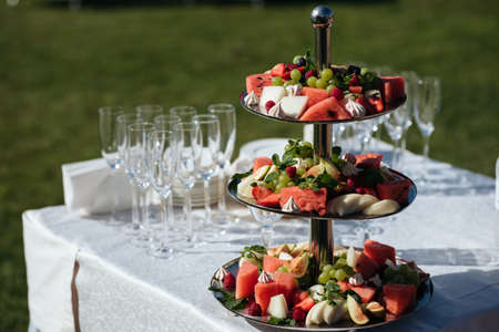 delicious fruit table with different sweets, for wedding reception, catering in restaurant
