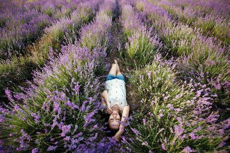 Smiling girl lie in a lavender field on sunset Standard-Bild
