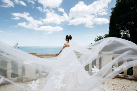 Girl in white wedding dress with big waves on the sea background