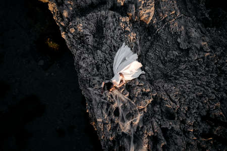 beautiful and young bride in white dress lying on big stone