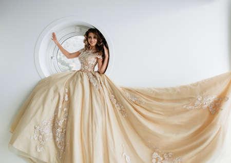 Beautiful woman in golden wedding dress sit on window in loft interior.