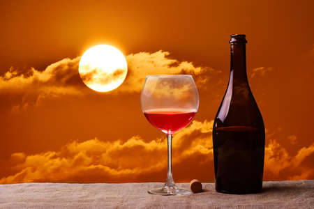 Red wine in glass, bottle and orange sunset