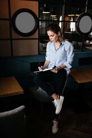 Pretty woman thinking and make records in daily planner. Casual style clothes