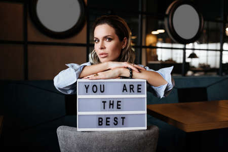 Girl holds a sign with the words you are the best. Pretty woman with makeup
