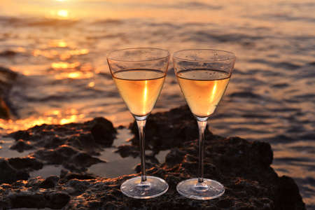 Two glasses with white wine on sthe stone near the sea. Golden sunset