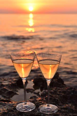 2 glasses with white wine on sthe stone near the sea. Golden sunset Standard-Bild
