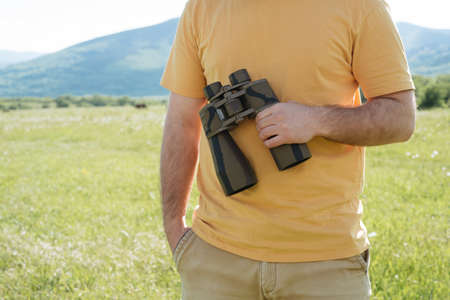 Man holds binoculars in the nature