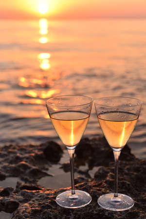 Pair of glasses with wnite wine near the sea at sunset. Standard-Bild