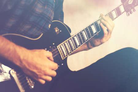 Playing electric guitar close-up, rocker