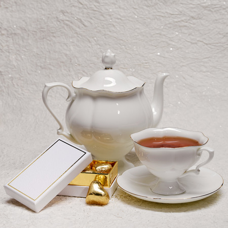 White porcelain teapot and cup of tea and a box of gold candies photo
