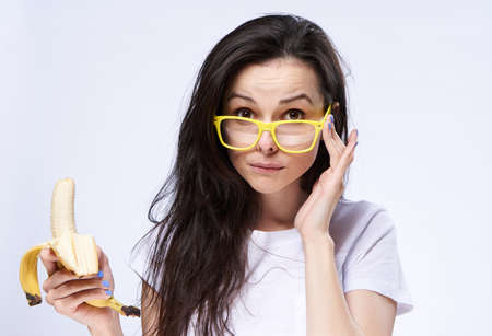 Woman in glasses with a banana on a light background.