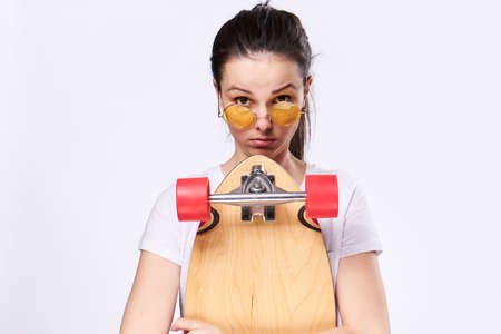 longboard: Woman in glasses with a skateboard on a pink background. Stock Photo