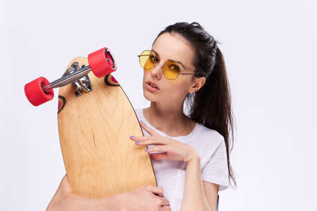building feature: Woman holds a skate, woman with glasses on a light background.