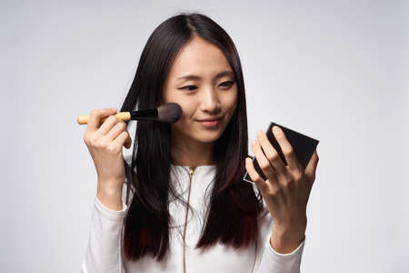 preening: A woman preening up. Woman with a cosmetic brush. The woman looks in a mirror on a gray background. Stock Photo