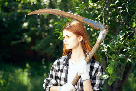 Woman with scythe, woman running in the garden. Stock Photo