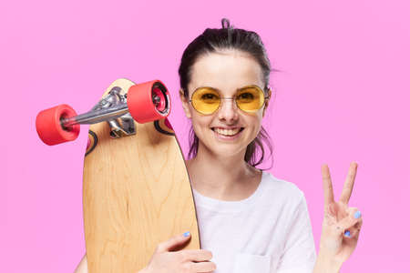 building feature: Woman in glasses with a skateboard on a pink background. Stock Photo
