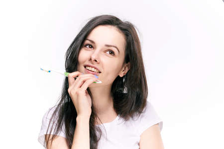 Woman dreaming, woman with toothbrush on isolated background portrait.