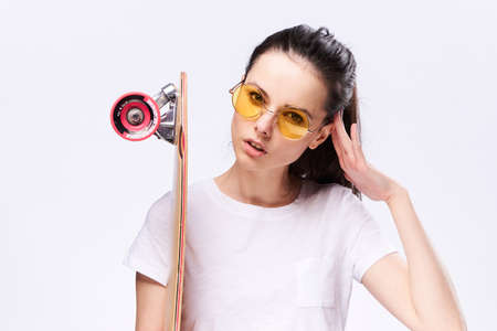 Woman in glasses holds a skate on a light background.