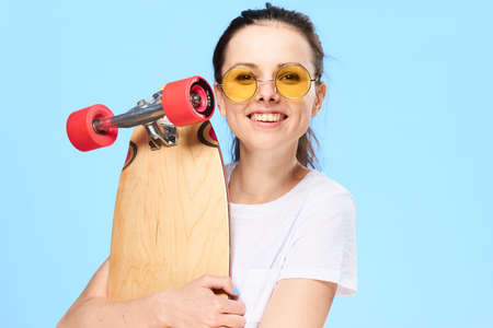 A woman with a skateboard and wearing glasses on a blue background. Stock Photo