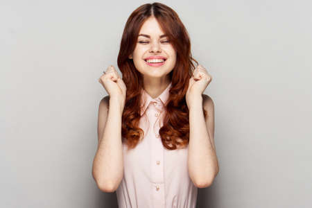 Cheerful woman, the woman squinted against a gray background. Stock Photo