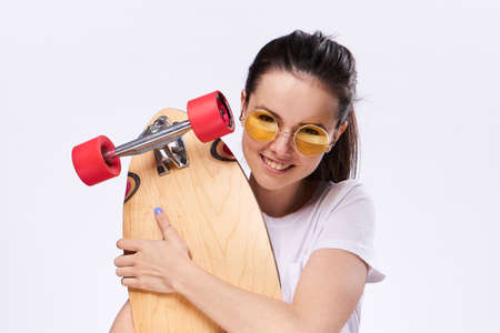 Woman holds a skate, woman with glasses on a light background.