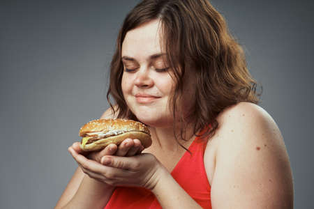 Hungry woman sniffing a hamburger on a gray background. Stock Photo
