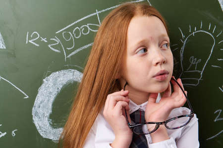 Schoolgirl thoughtful and holds glasses on the background of a school board.