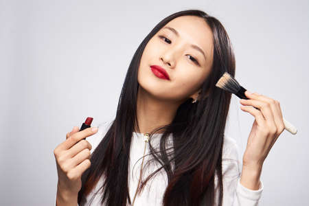 Woman with red lips, woman with lipstick and cosmetic brush on gray background. Stock Photo