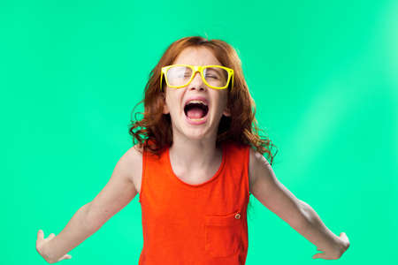 Girl with open mouth, girl on green background. Stock Photo